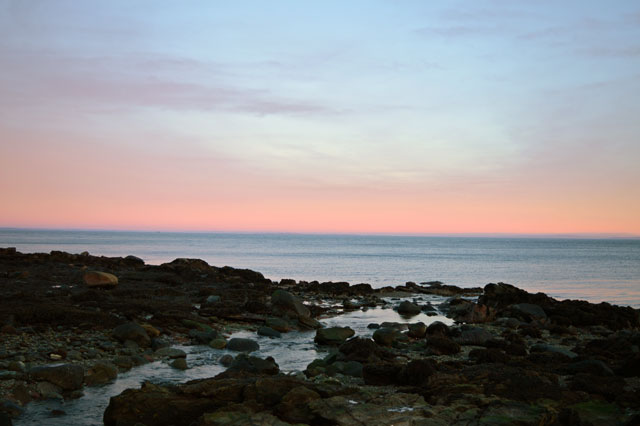 Rocky-shore,-sunset-sky